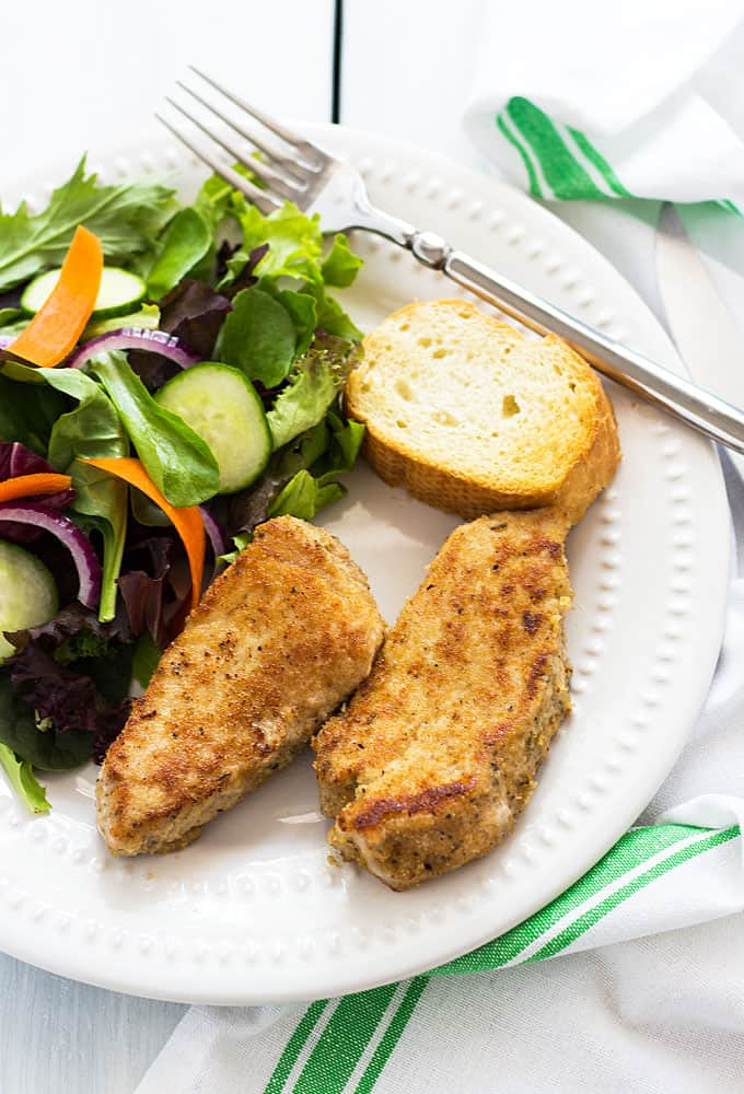 Overhead view of two slices of Parmesan crusted pork loin with a salad and bread on a white plate.