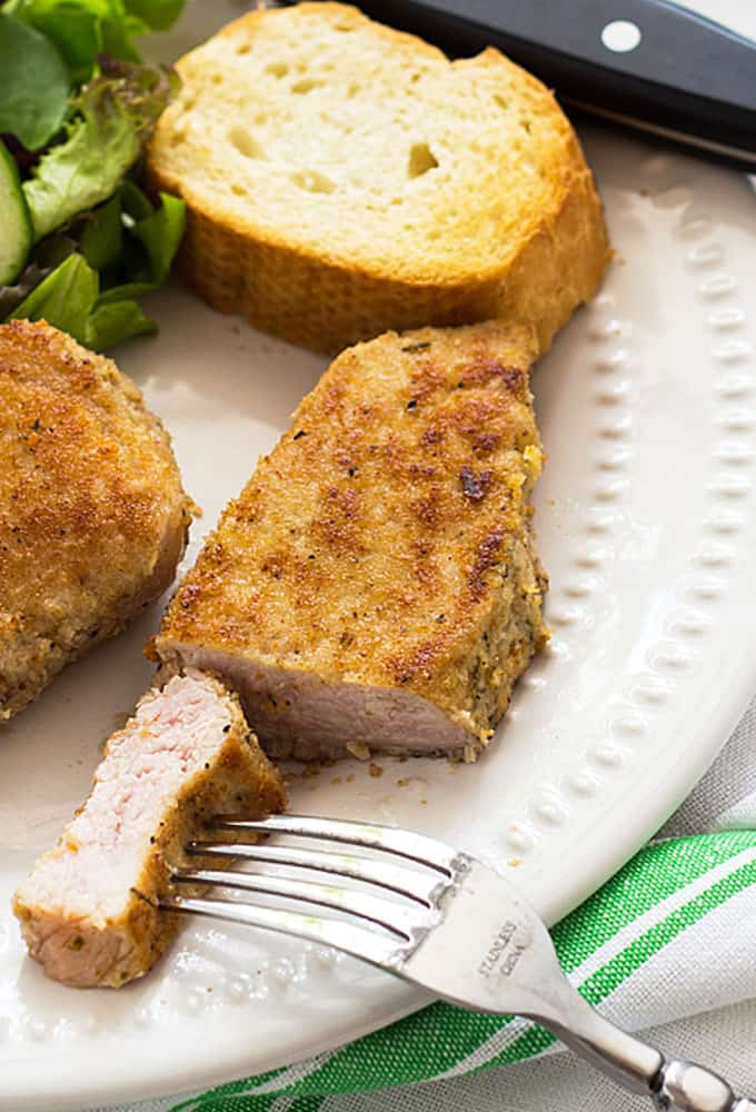 Closeup view of sliced parmesan crusted pork loin filet on a white plate with a fork.