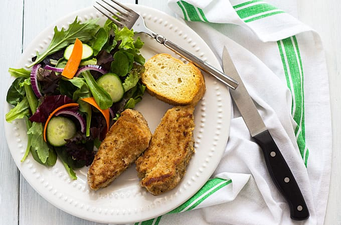 Overhead view of two Parmesan crusted pork medallions, salad and bread on a white plate.