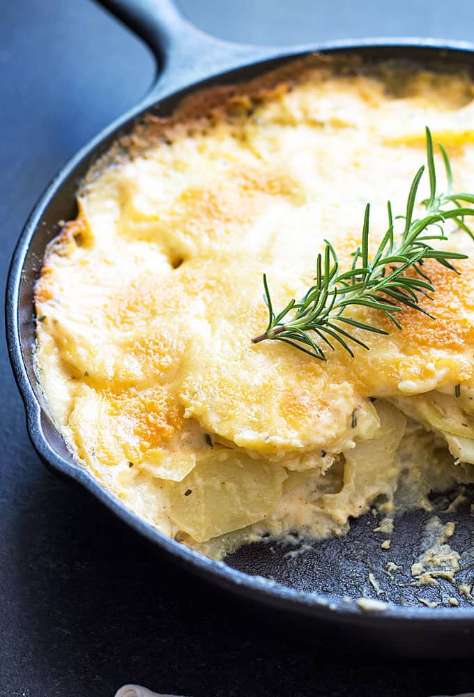Closeup view of au gratin potatoes in a skillet with some of the potatoes removed.
