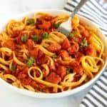 Pasta with tomato sauce topped with parsley in a white bowl with a fork beside a black and white striped napkin.