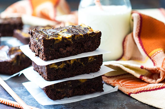 Front view of three stacked brownies by a patterned napkin and a glass of milk.