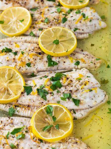 A closeup of baked flounder fillets in a baking dish with sliced lemons.