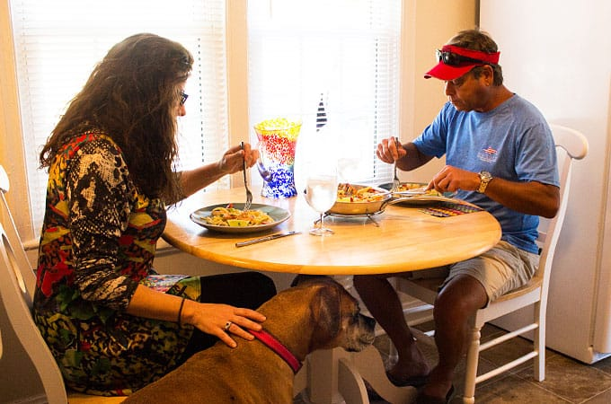 A couple seated and eating dinner at a small kitchen table.  A dog is standing by the woman.