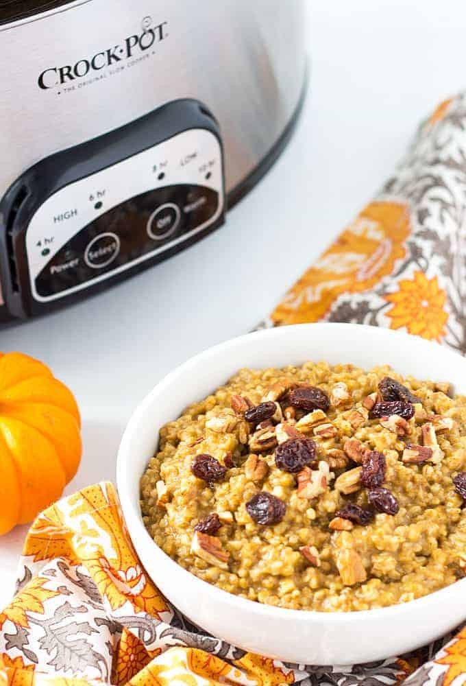 Pumpkin flavored oatmeal in a white bowl topped with raisins and pecans.