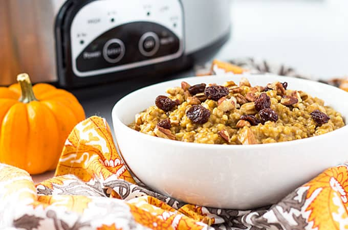 Front view of a bowl of oatmeal. A small pumpkin and slow cooker are in the background.
