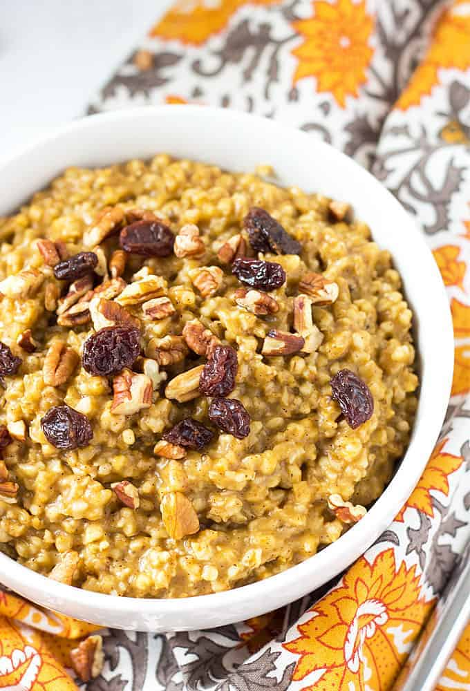 Overhead closeup view of a white bowl of oatmeal topped with raisins and pecans on a patterned napkin.