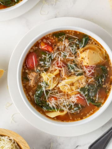Overhead closeup view of a bowl of tortellini soup with sausage and spinach.