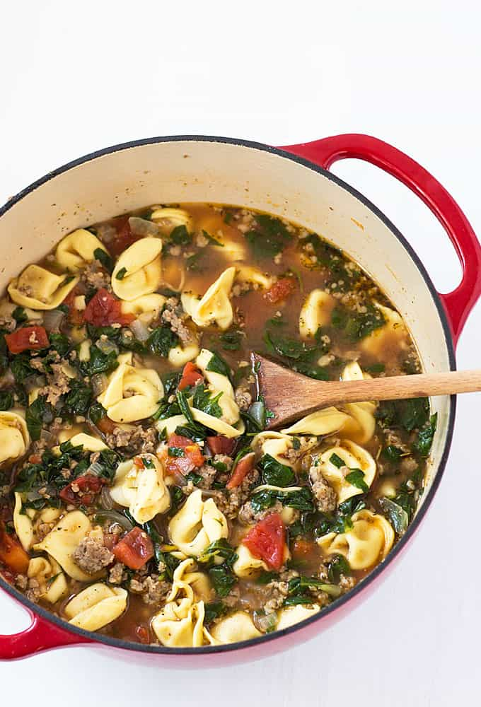 Overhead view of Italian sausage tortellini soup in a red dutch oven with a wooden spoon.