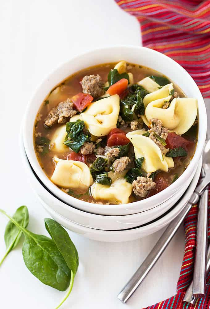 Overhead view of Italian sausage and tortellini soup with spinach in a white bowl on a white surface.