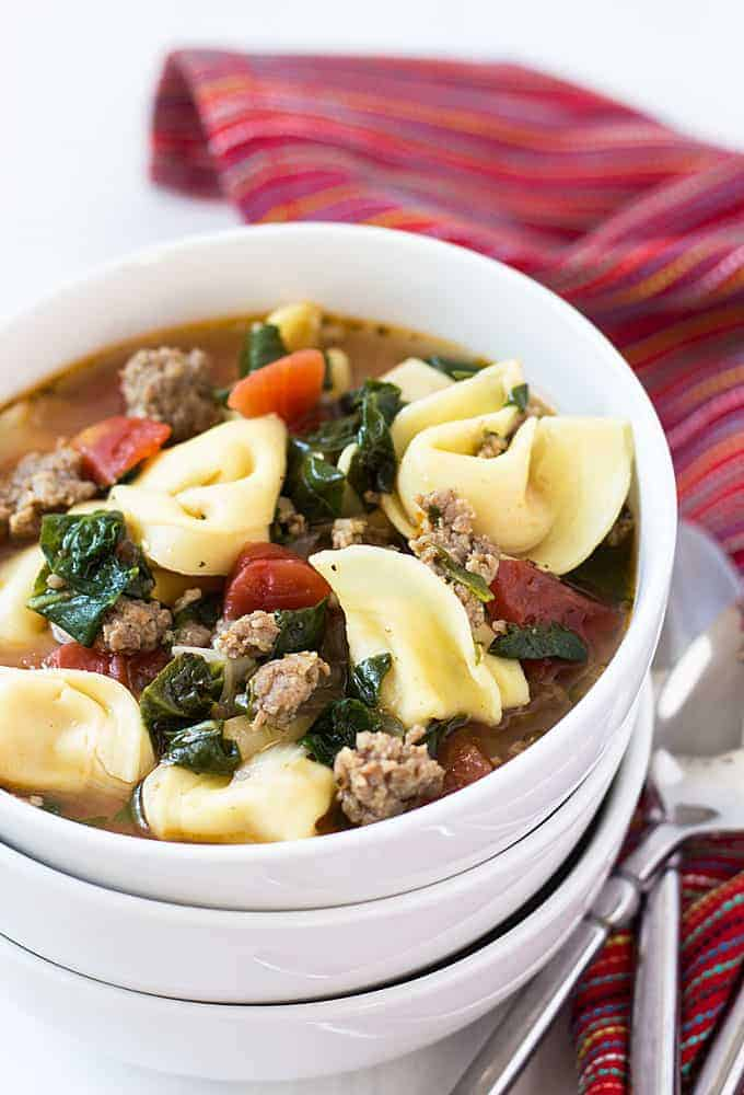 Soup with sausage, spinach and tortellini in a white bowl beside a striped napkin.