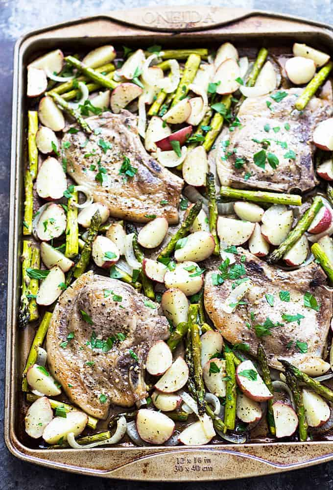 Overhead view of baked pork chops, asparagus and red potatoes on a baking sheet.