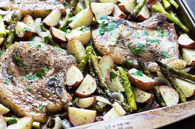 Overhead closeup view of baked pork chops and vegetables on a baking sheet.