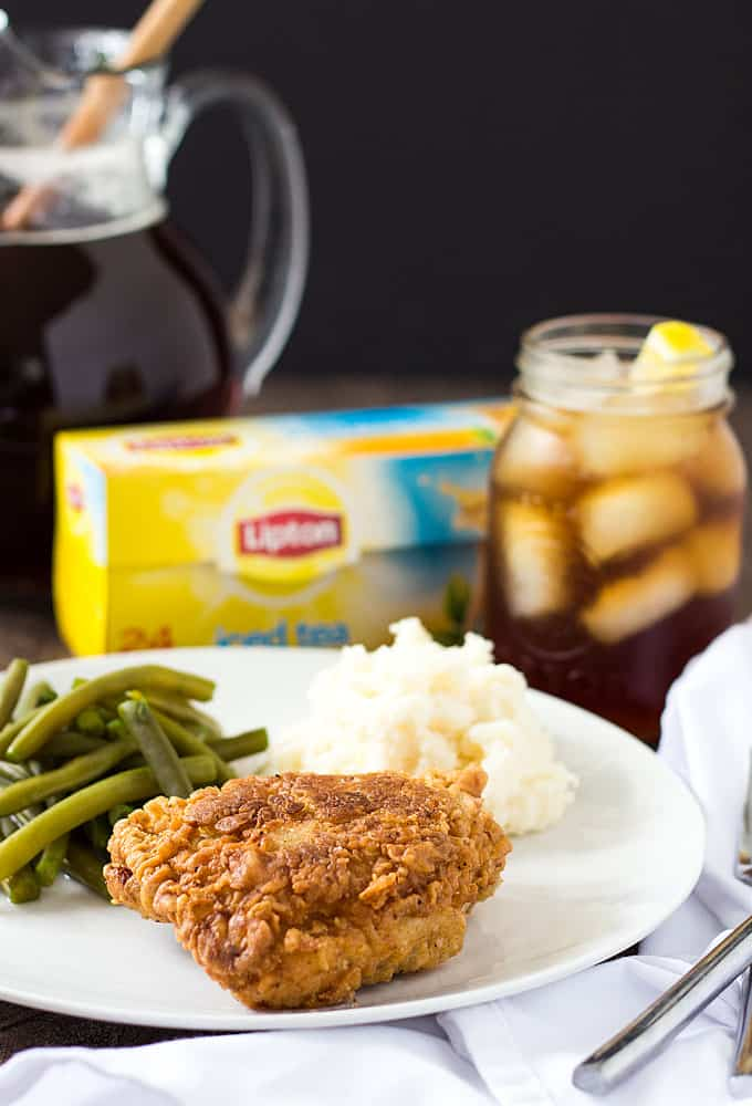 A fried chicken thigh, green beans and mashed potatoes on a white plate by a glass of tea.