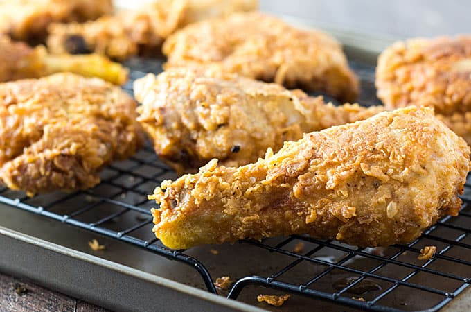 Front closeup view of fried southern dark meat chicken on a wire rack.