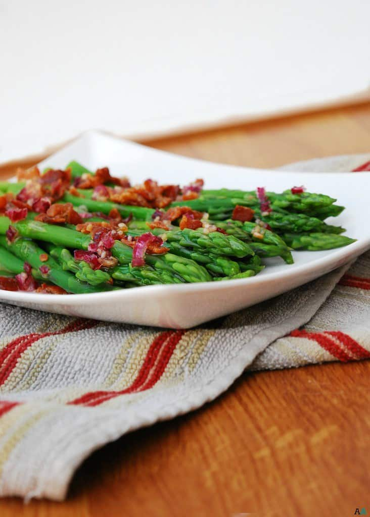 Front view of asparagus spears with bacon and red onion vinaigrette in a square white dish.