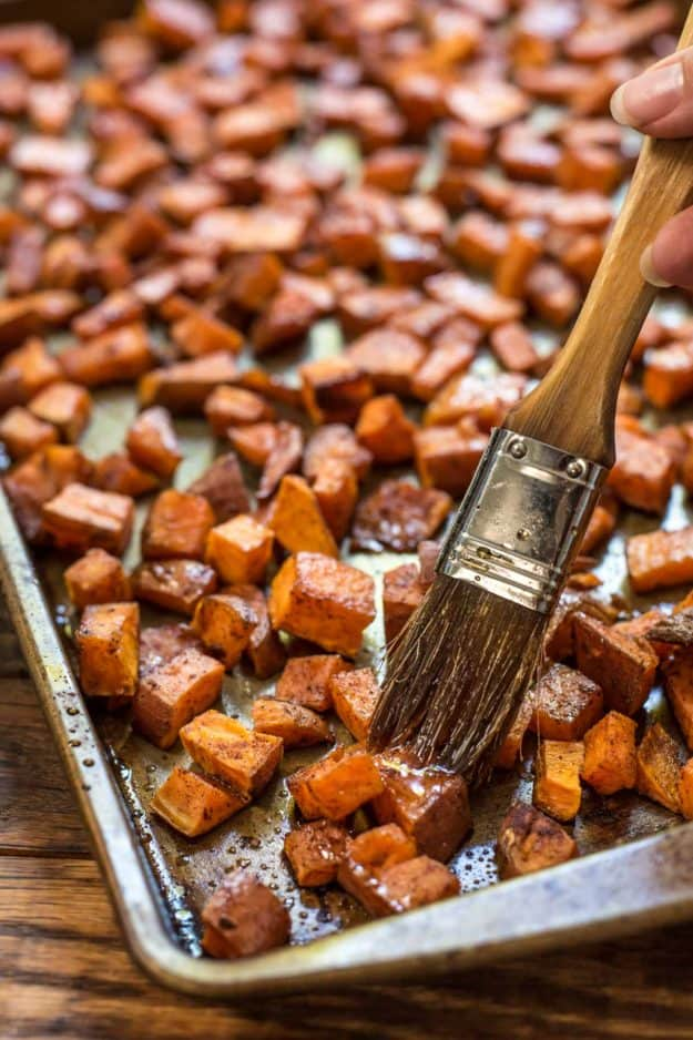 A basting brush brushing maple glaze on chopped sweet potatoes in a baking pan.