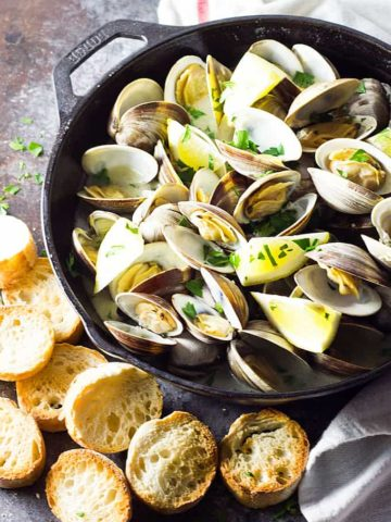 Overhead view of steamed clams in a cast iron skillet by sliced French bread.
