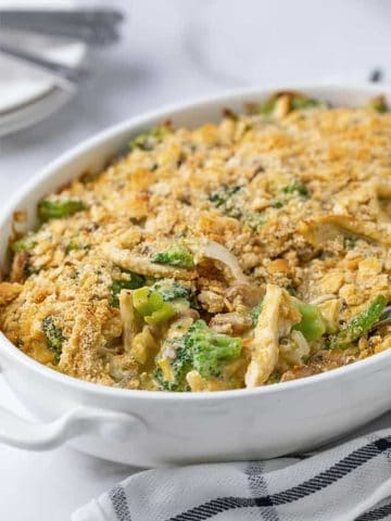 Chicken casserole topped with crushed crackers in an oval white baking dish beside a black and white checked napkin.