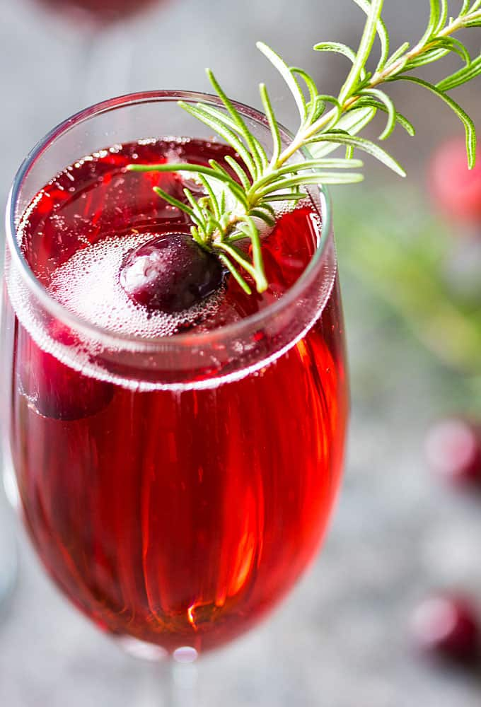 A closeup view of the top of a mimosa with a rosemary sprig and a cranberry in a champagne glass.