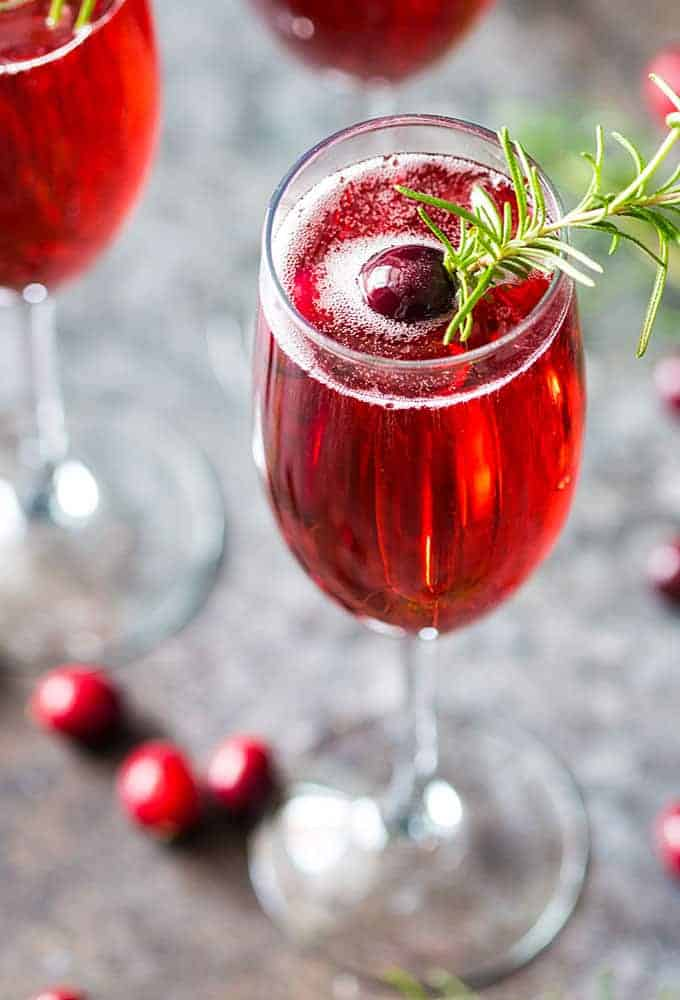 Closeup view of a cranberry mimosa garnished with rosemary and fresh cranberries.