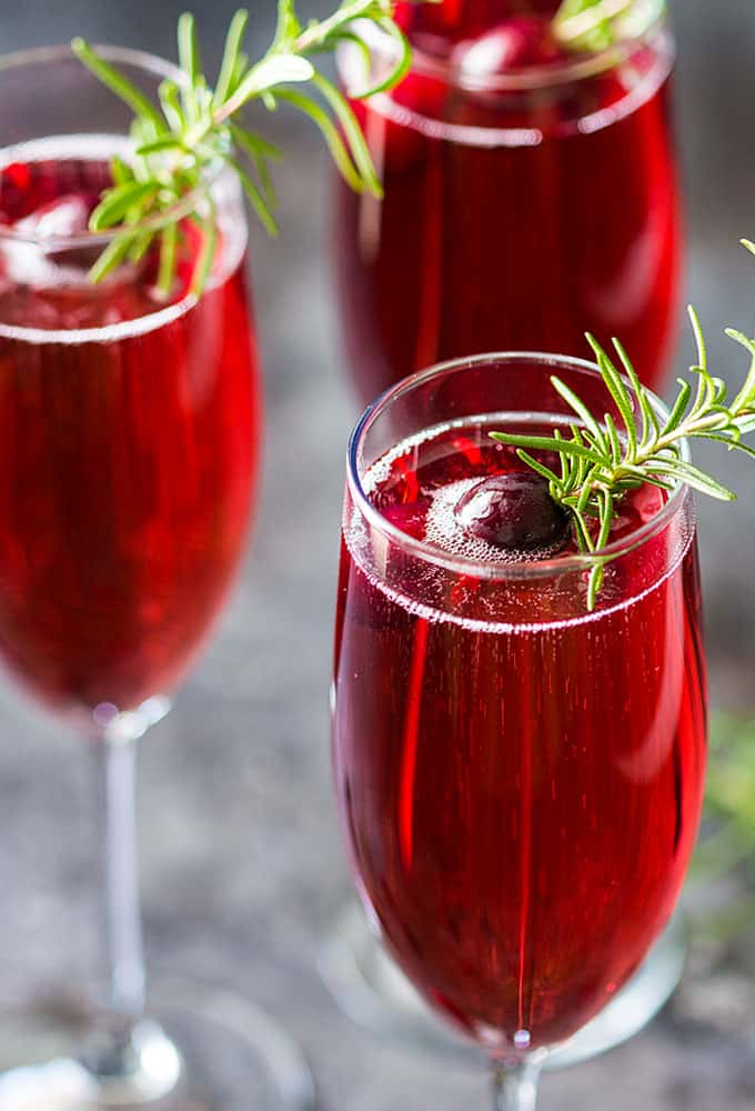 Closeup view of three mimosas garnished with rosemary sprigs and cranberries.
