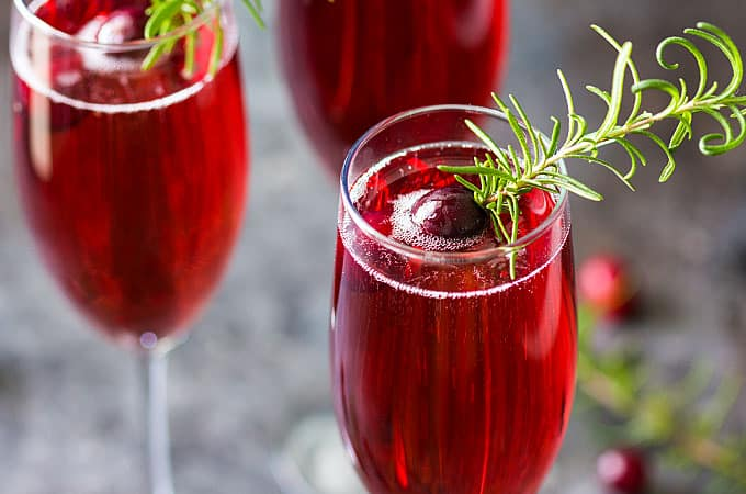 Front view of three garnished cranberry mimosas in champagne flutes.
