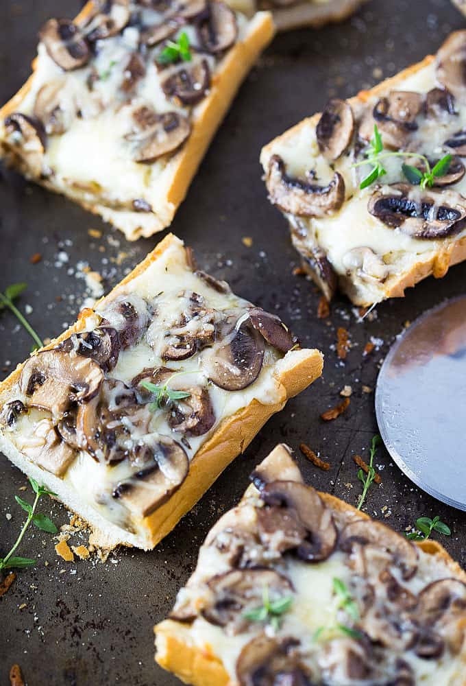 Overhead view of four slices of french bread pizza with mushrooms.