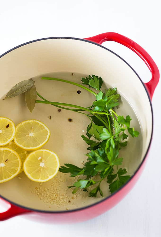 Overhead view of a red dutch oven with water, peppercorns, garlic, parsley, lemon and bay leaves.
