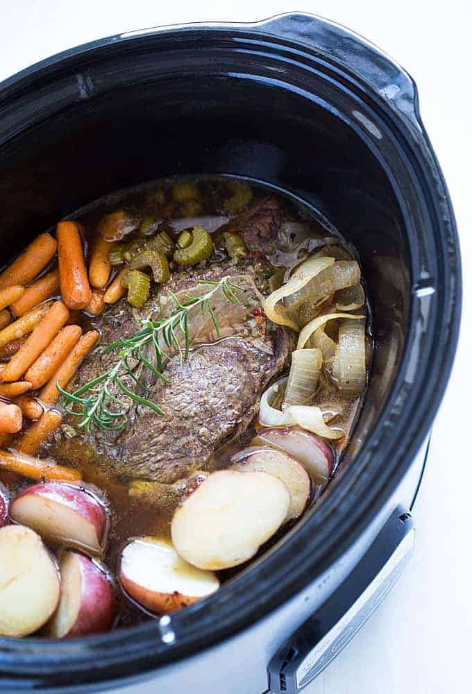A cooked roast with carrots, potatoes, celery and onions in an oval slow cooker.