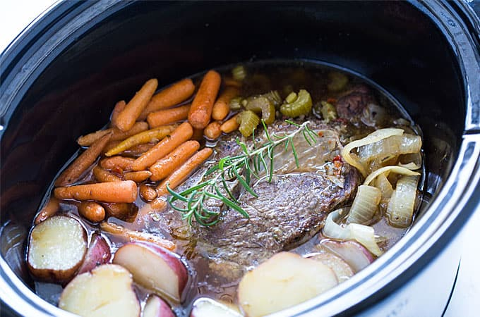 A cooked pot roast with vegetables in a black oval crock pot insert.