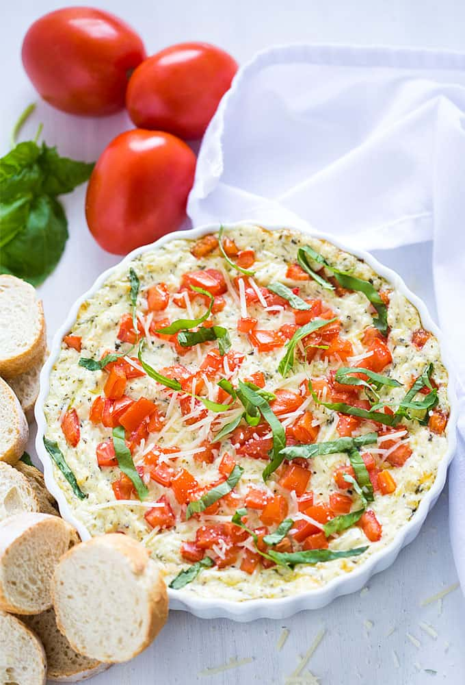 Overhead view of dip topped with diced tomatoes and basil in a white baking dish.