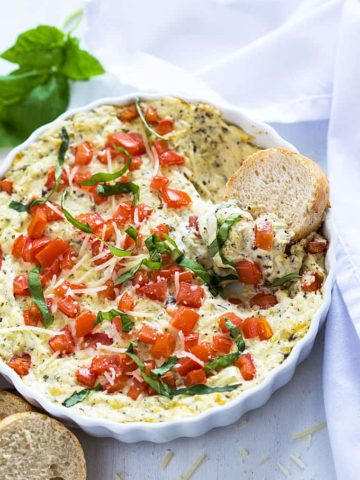 Overhead view of hot cheesy caprese dip in a white baking dish.