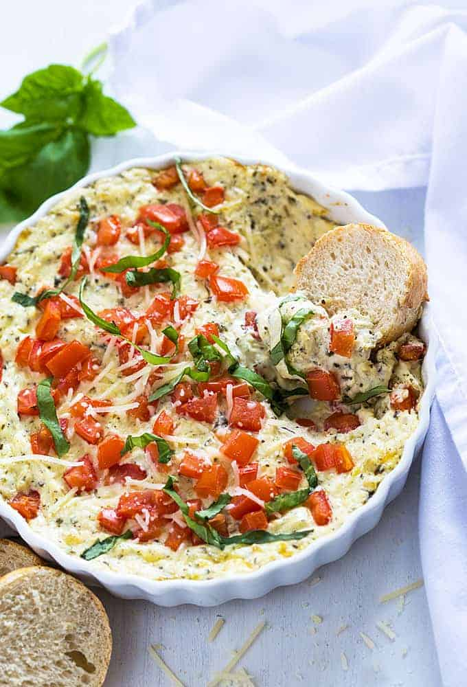 Overhead view of caprese dip in a round white dish with a slice of French bread in the dip.