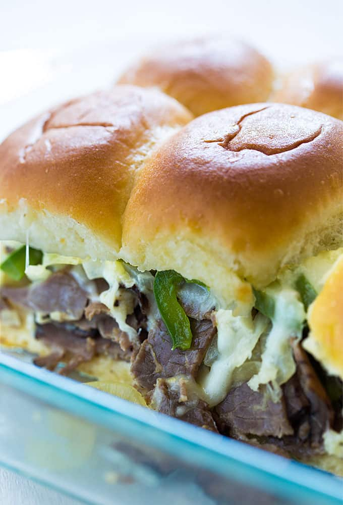 Closeup view of baked cheese steak sliders in a glass baking dish.
