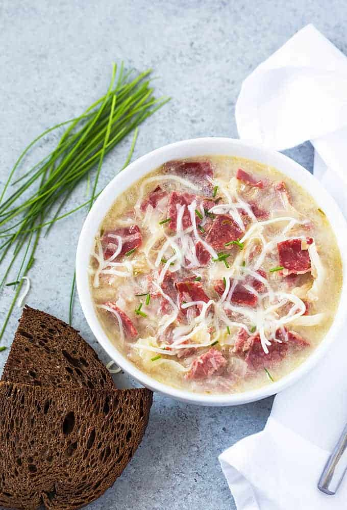 Overhead view of a white bowl of Reuben soup by rye bread and chives.
