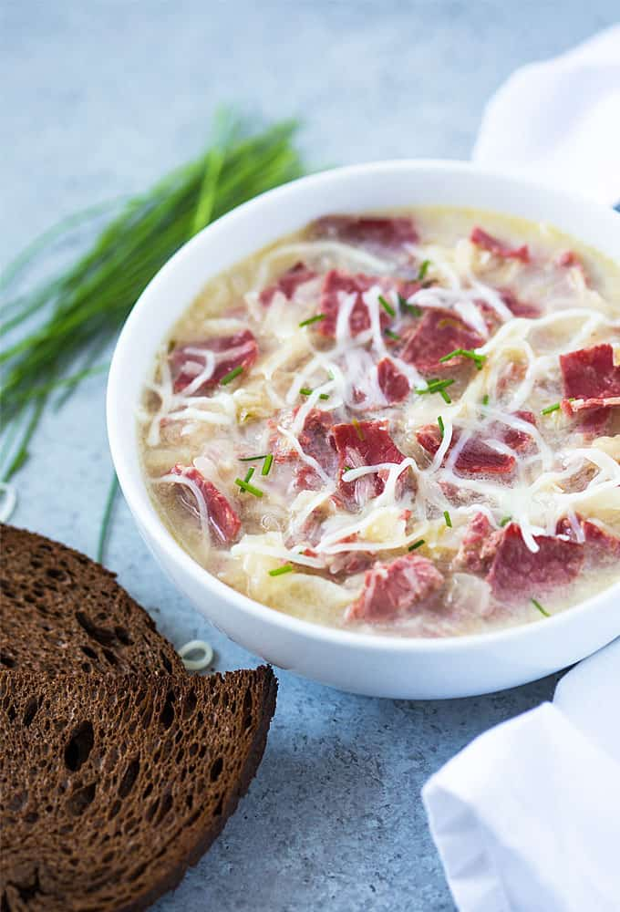 Front closeup view of soup with corned beef, sauerkraut and Swiss cheese in a white bowl.