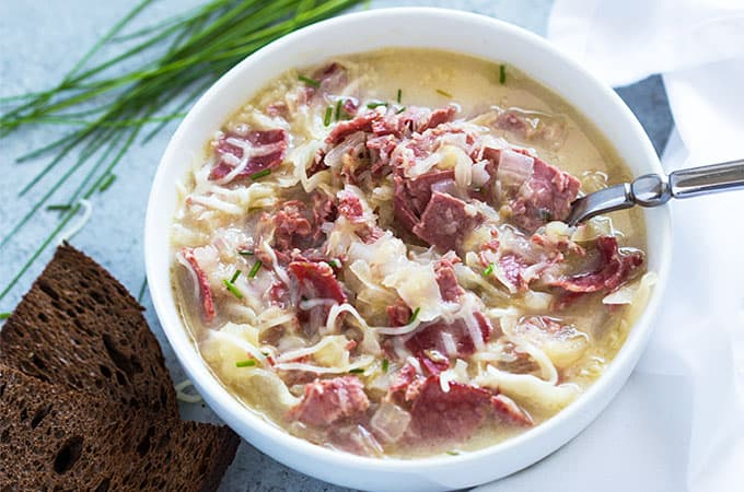 Overhead closeup view of a white bowl of creamy Reuben soup with a spoon.