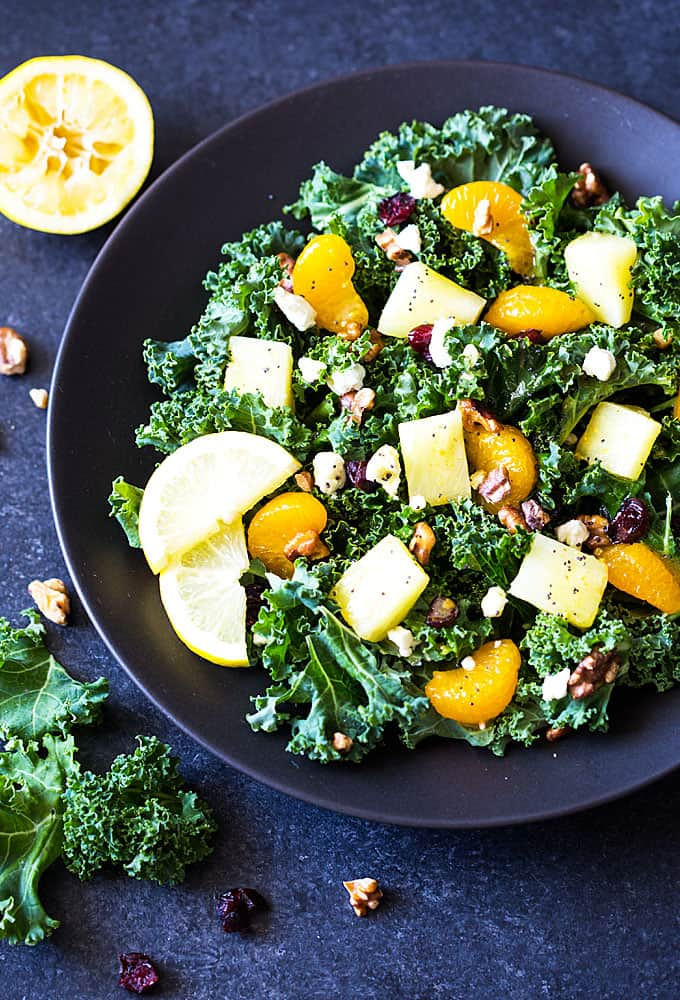 Overhead view of a kale salad with fruit, walnuts and feta cheese on a black plate.