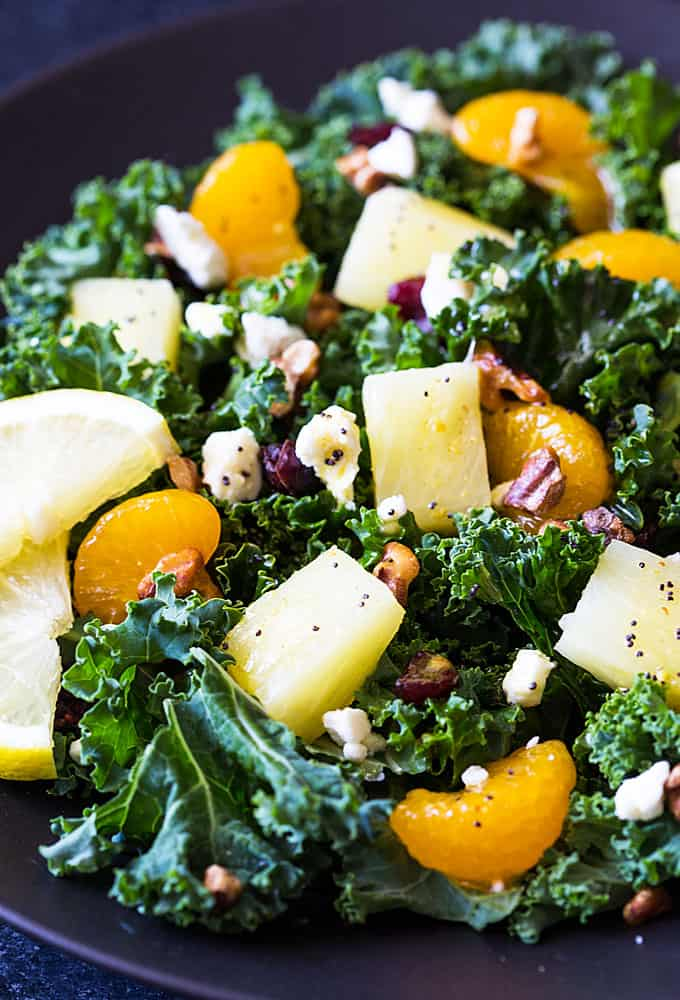Closeup view of a salad with kale, pineapple, mandarin oranges, cranberries, walnuts and feta cheese.
