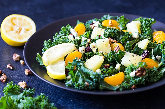 Kale and fruit salad drizzled with a vinaigrette on a black plate on a dark background.