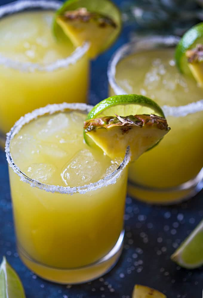 Three margaritas in glasses garnished with fresh pineapple and lime.