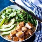 Overhead view of salmon noodle bowl with vegetables in a white bowl