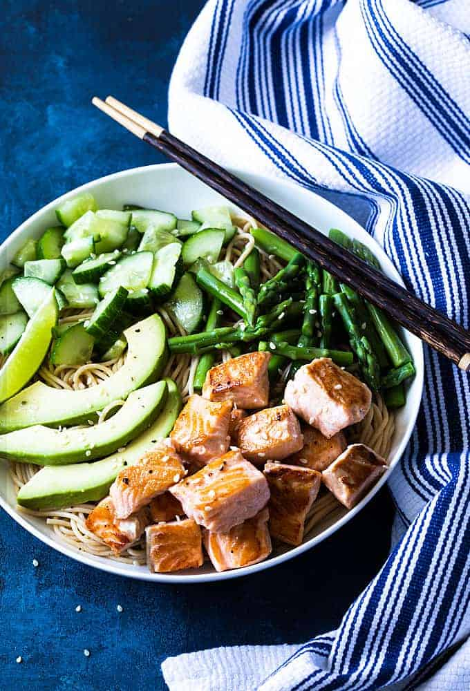 Overhead view of salmon noodle bowl with asparagus, sliced avocado and cucumber in a white bowl