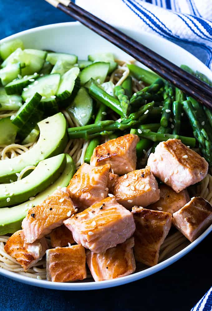 Closeup of salmon noodle bowl with vegetables in a white bowl with chopsticks