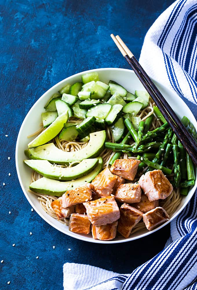 Overhead view of salmon and whole grain noodles with asparagus, avocado and cucumber in a white bowl
