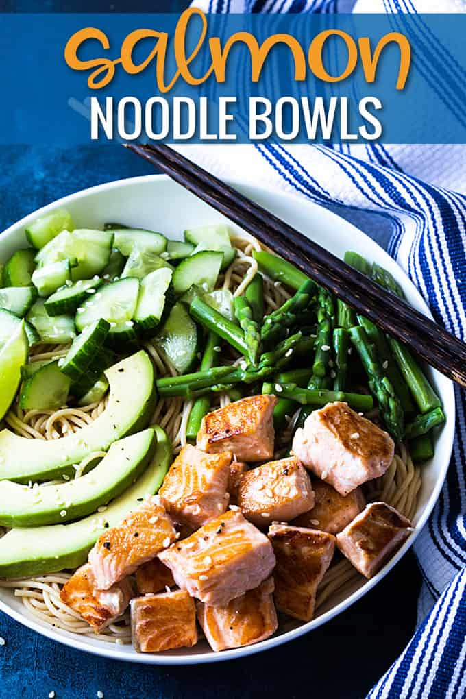Overhead closeup view of salmon and vegetables over noodles in a white bowl with chopsticks.