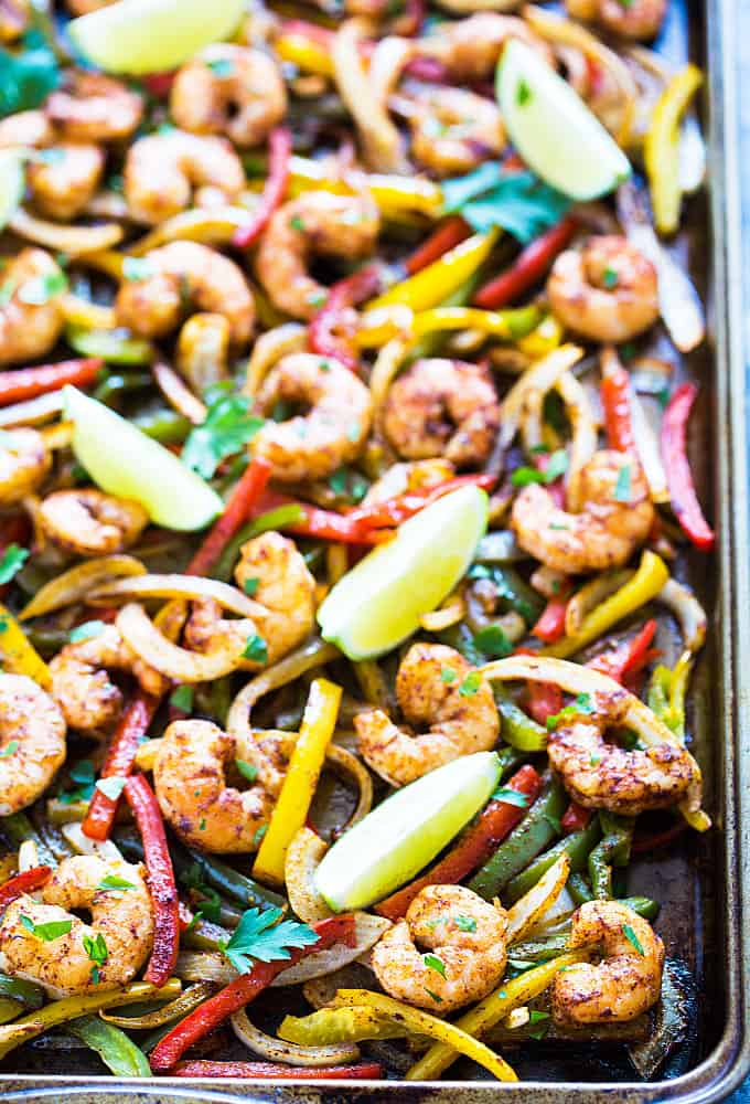 Shrimp fajita mixture on a baking sheet topped with cilantro and lime wedges.