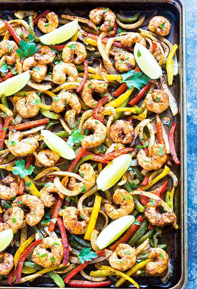 Overhead view of seasoned shrimp, peppers, onions and lime wedges on a baking sheet.