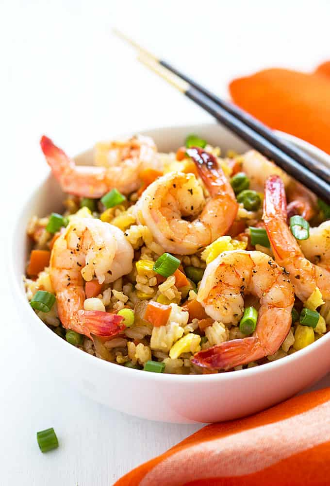 Front view of fried rice with shrimp in a white bowl with a set of chopsticks.